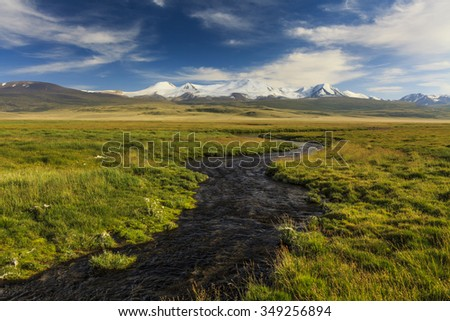 Green meadows and river on the background of mountain scenery. - stock photo