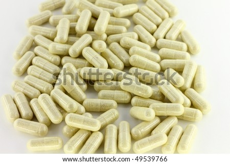 Green medication capsules on white background
