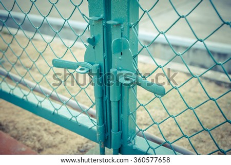 Green metal fence lock with pastel tone - stock photo