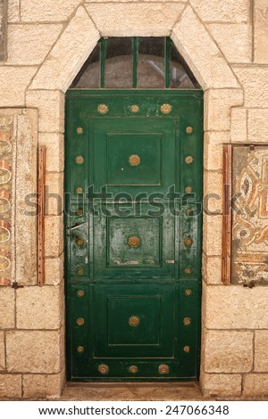 Green metal forged door of sandstone ancient building, Middle east. Architectural theme. - stock photo