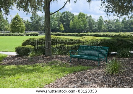 Green metal park bench surrounded by nature - stock photo