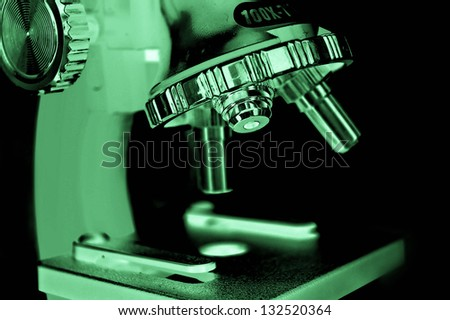 green microscope over black background - stock photo