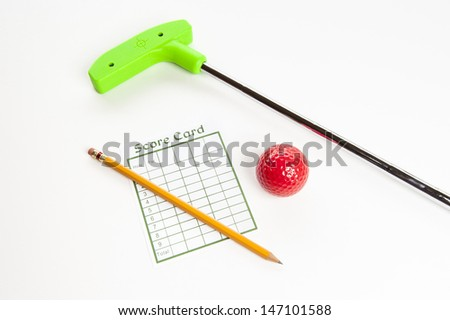 Green mini golf club with score card, pencil  and red ball - stock photo