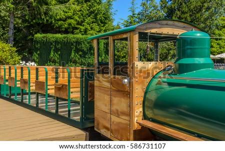 Green mini train with wooden cars in adventure park at sunny summer day.