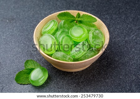 Green mint candy in a wooden bowl on a dark background - stock photo