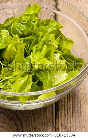 green mixed salad in glass bowl on wooden table background