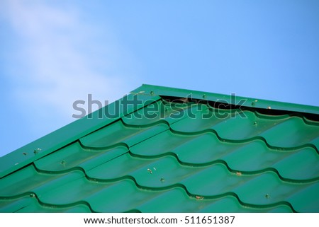 Green Modern Roof Covered With Tile Effect PVC Coated Metal Roof Sheets  Against A Blue Sky