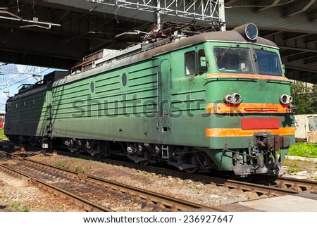 Green modern Russian locomotive with red stripes on the cabin stands on the railway station