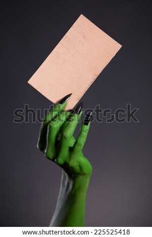 Green monster hand holding blank piece of cardboard, horror Halloween theme   - stock photo