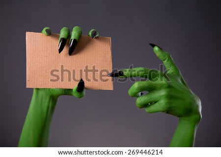 Green monster hands with black long nails pointing on blank piece of cardboard, Halloween theme   - stock photo