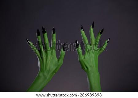 Green monster hands with sharp black nails, Halloween theme, studio shot on black background  - stock photo