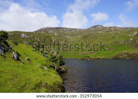 green mountain and a loch in the Highlands of Scotland - stock photo