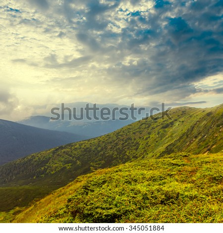 green mountain landscape under a dense clouds - stock photo