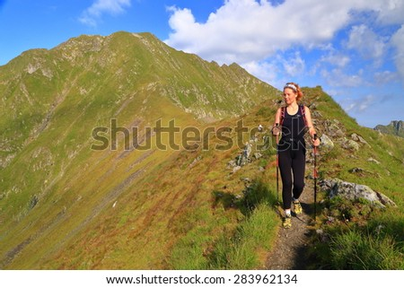 Green mountain slope traversed by woman hiker in sunny morning - stock photo