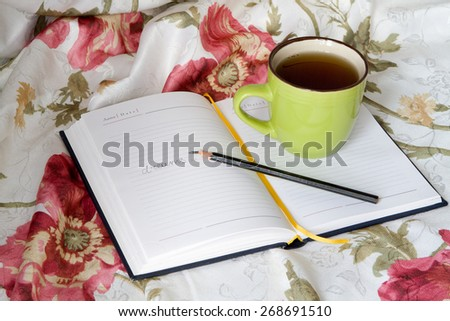 Green mug with tea or coffee in bed with bedding with floral print diary with a pencil or pen note thoughts dreams broken record broken - stock photo