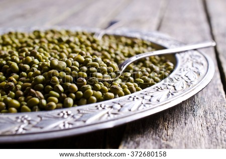 Green mung beans in a bowl on a wooden background. Selective focus.