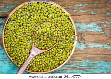 Green mung beans in wooden spoon with ceramic bowl  - stock photo