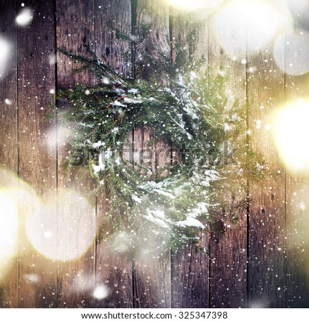 Green Natural Wreath on Wooden Background with drawing Falling Snow. Toned image with Light Boke - stock photo