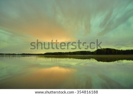 Green northern lights (Aurora Borealis) in the night sky over a beautiful lake in Finland. Vibrant colors on the sky and symmetric reflections on the still water of the lake. - stock photo