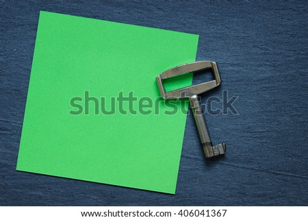 Green note with vintage key on dark background
