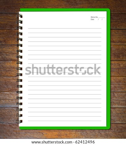Green notebook (blank paper) on wood wall.