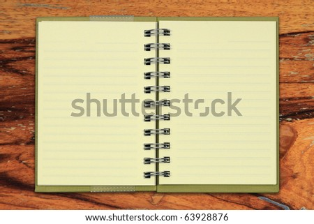 Green notebook isolated on wooden background.
