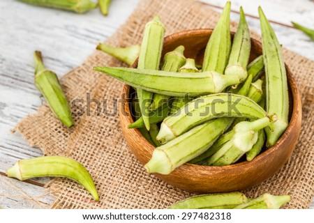 Green okra vegetable on linen napkin against white wooden background - stock photo