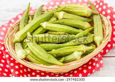 Green okra vegetable on red napkin against white wooden background - stock photo
