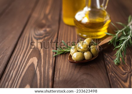 green olives and olive oil on wooden table - stock photo
