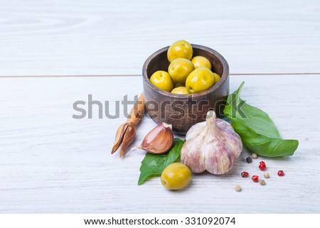 Green olives, basil, garlic and oil - stock photo