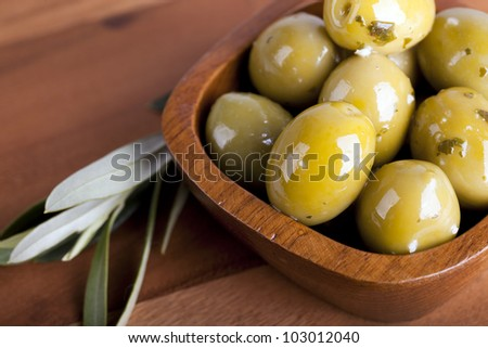 Green olives in a wooden bowl with olive branch, on wooden background. - stock photo