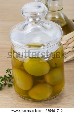 Green olives in the bowl with thyme branch