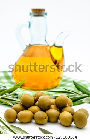 Green olives,  olive oil and olives leaves on a white background