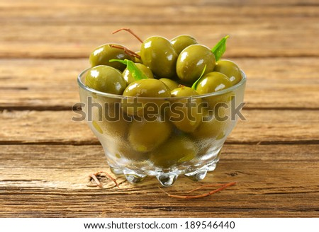 green olives pickled in oil, served in the glass bowl - stock photo