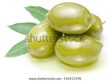 Green olives with leaves in oil isolated on a white. - stock photo