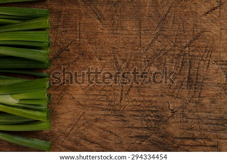 Green onion sticks on rustic wooden table, left side - stock photo