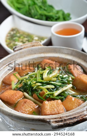 Green onions with chicken tofu in clay pot - stock photo
