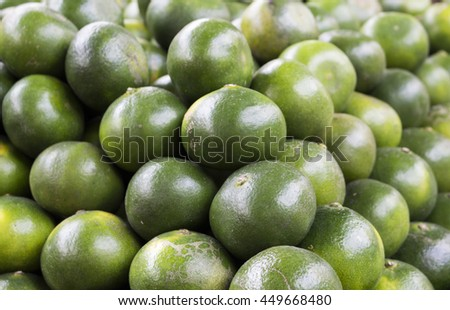 Green orange background. Close-up lime pile on table. Green ripe lime with glossy surface backdrop. Fresh summer wallpaper. Philippines kalamanchi exotic fruit. Tropical garden harvesting. Lime skin - stock photo
