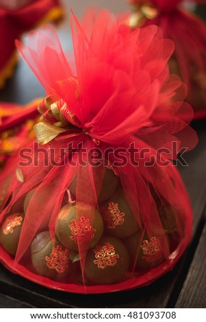 "green orange coved by red fabric. Object in Thai-Chinese Wedding traditional. Vegetable for engagement with text meaning ""happy"" on green banana in red cover"