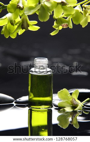 Green orchid and massage oil on therapy stones