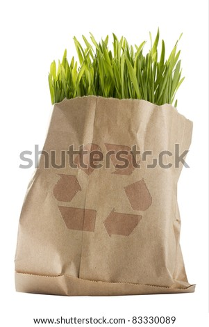 Green organic wheat grass in a brown bag with a recycle symbol.