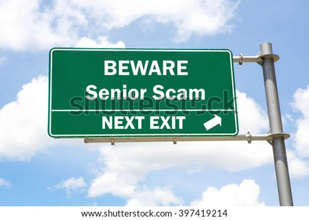 Green overhead road sign with a Beware of a Senior Scam Next Exit concept against a partly cloudy sky background. - stock photo