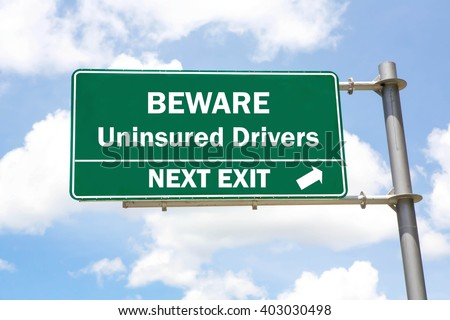 Green overhead road sign with a Beware of Uninsured Drivers Next Exit concept against a partly cloudy sky background. - stock photo