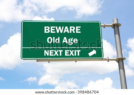 Green overhead road sign with a Beware Old Age Next Exit concept against a partly cloudy sky background. - stock photo