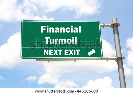 Green overhead road sign with a Financial Turmoil Next Exit concept against a partly cloudy sky background. - stock photo