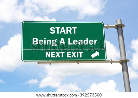 Green overhead road sign with a Start Being A Leader Next Exit concept against a partly cloudy sky background. - stock photo