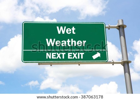 Green overhead road sign with a Wet Weather Next Exit concept against a partly cloudy sky background. - stock photo