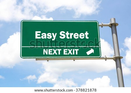 Green overhead road sign with an Easy Street Next Exit concept against a partly cloudy sky background. - stock photo