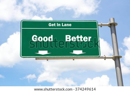 Green overhead road sign with the instruction to get in lane with a Good or Better concept against a partly cloudy sky background. - stock photo