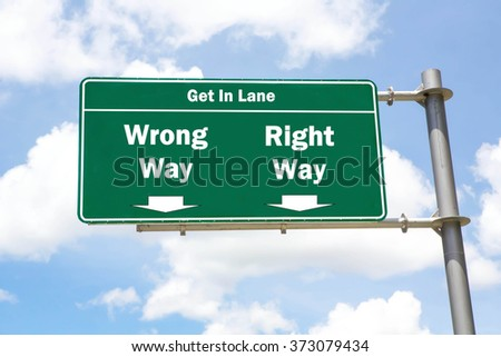 Green overhead road sign with the instruction to get in lane with a Wrong Way or Right Way concept against a partly cloudy sky background. - stock photo